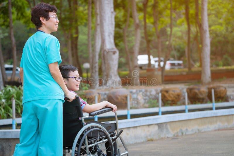 Lächelnde ältere Krankenschwester der Pflegekraft mach's gut einen Jungenpatienten im wheelc stockfotos