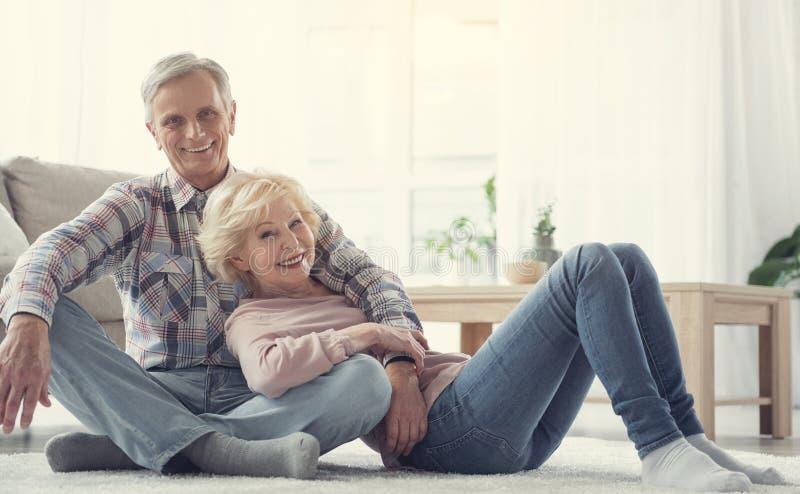 Lächelnde ältere Menschen, die auf dem Boden sich ausruhen lizenzfreies stockbild