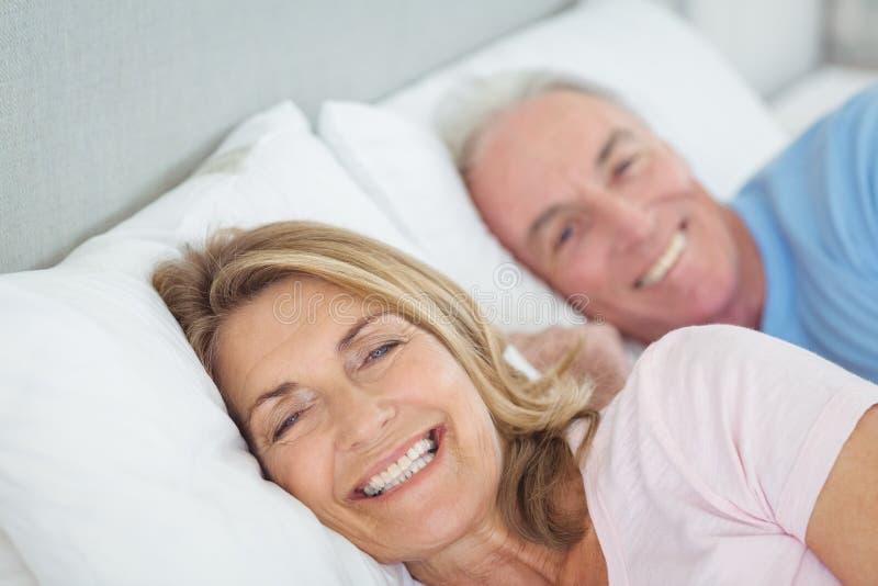 Lächelnde ältere Paare, die auf Bett liegen lizenzfreies stockbild