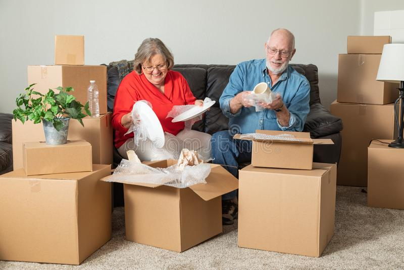 Lächelnde ältere Paare, die bewegende Kästen verpacken oder auspacken stockfotos