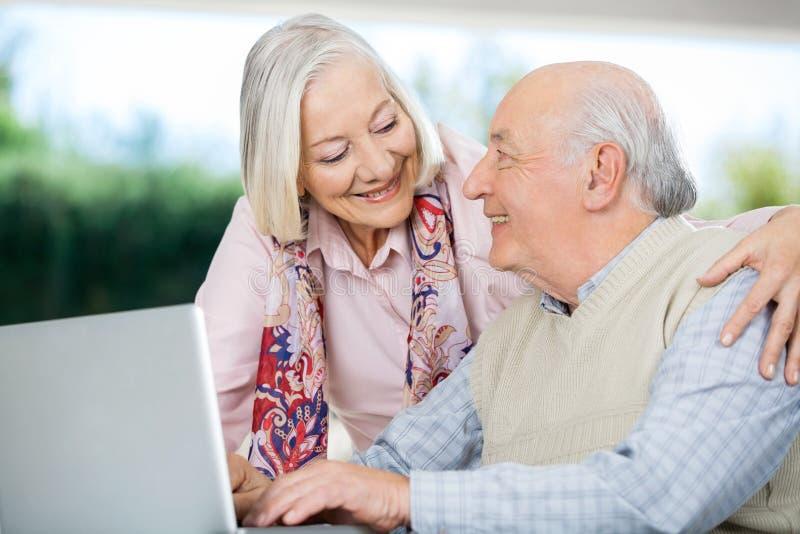 Lächelnde ältere Paare, die einander während betrachten lizenzfreie stockfotos