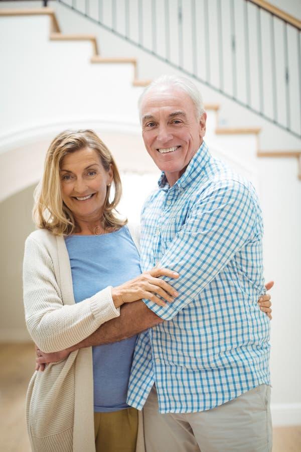 Lächelnde ältere Paare, die im Wohnzimmer sich umfassen stockbild
