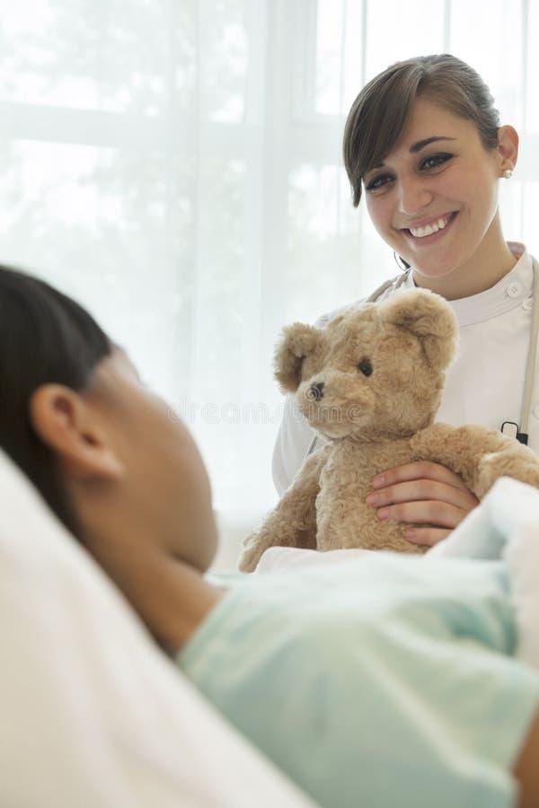 Lächelnde Ärztin, die einem Mädchenpatienten einen Teddybären sich hinlegt auf einem Krankenhausbett gibt lizenzfreies stockbild