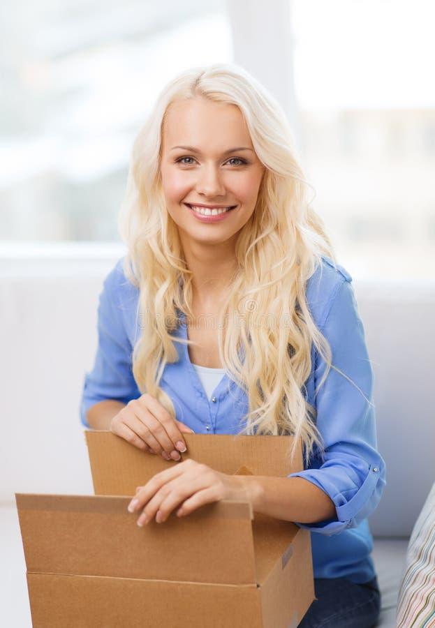 Lächelnde Öffnungspappschachtel der jungen Frau zu Hause lizenzfreie stockfotos