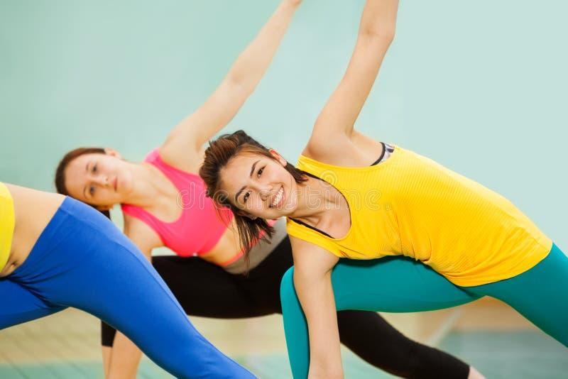 Lächelnde übende Gymnastik der asiatischen Jugendlichen stockfoto