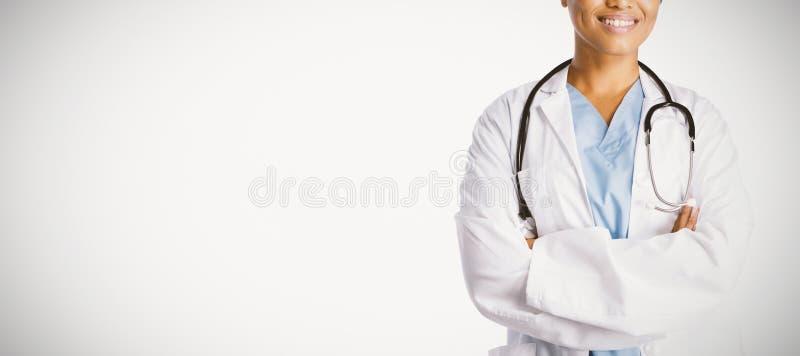 Lächelnde überzeugte Ärztin mit den gekreuzten Armen stockbild