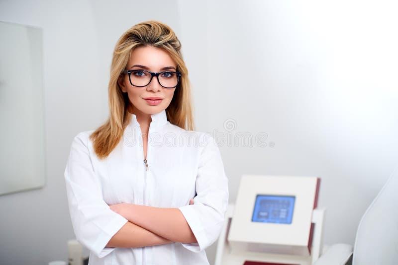 Lächelnde überzeugte Ärztin mit Laborkittel auf in ihrem Büro an stehen mit medizinischer Hardware und geduldigem Stuhl lizenzfreie stockfotos