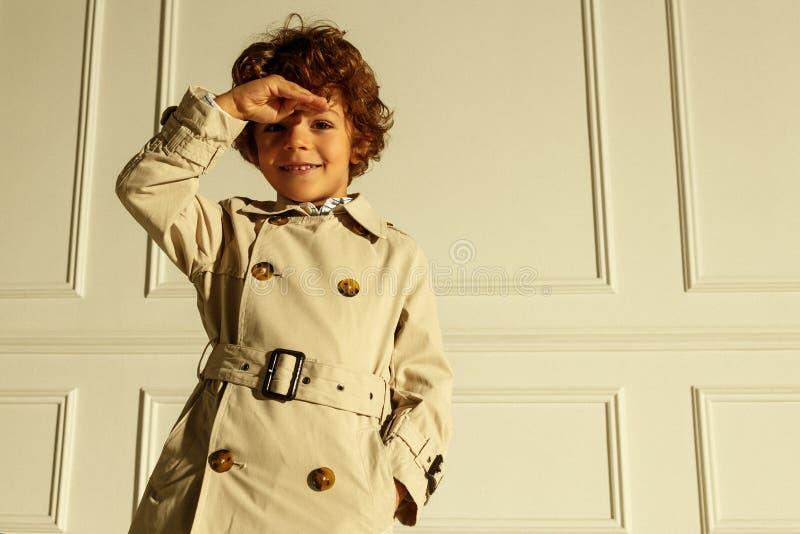 Lächelnde Abnutzung des kleinen Jungen im modernen Regenmantel, wirft überzeugtes im Studio, auf einer weißen neoklassischen Wand stockbild