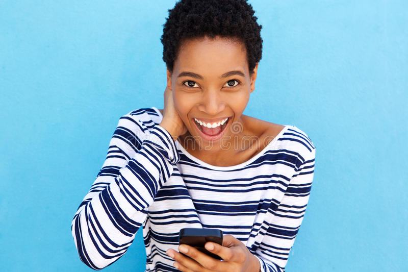 Lächelnde afrikanische Frau, die intelligentes Telefon hält stockfoto