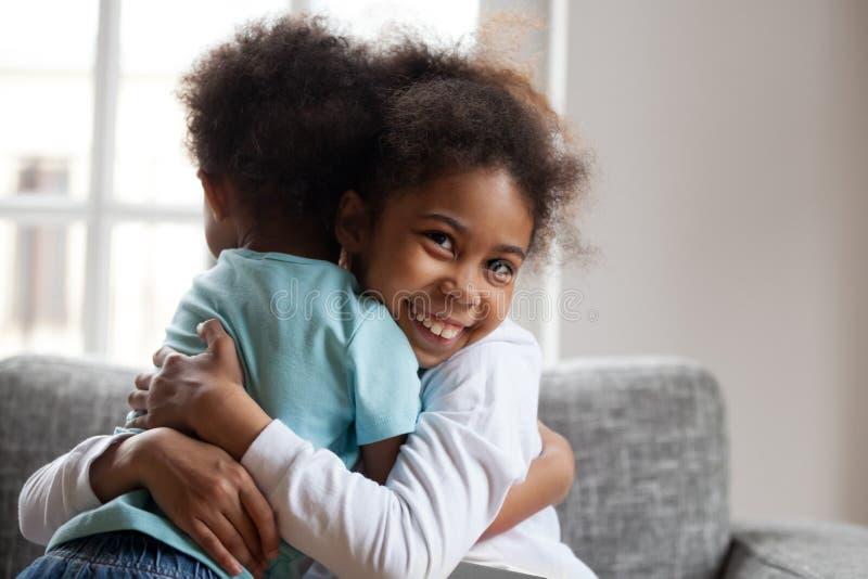 Lächelnde afrikanische Mädchenschwester, die zu Hause wenig Jungenbruder umfasst lizenzfreies stockbild
