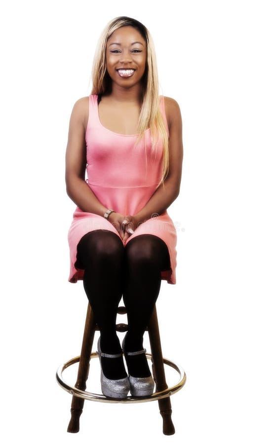 Lächelnde Afroamerikaner-Frau, die auf Schemel im Kleid sitzt stockfoto