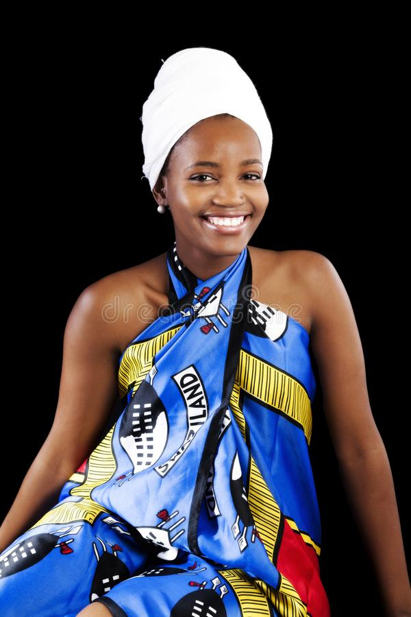 Lächelnde Afroamerikaner-Frau, die im bunten Kleid sitzt lizenzfreie stockbilder