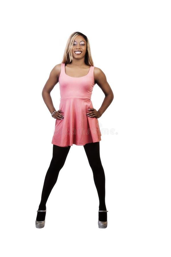 Lächelnde Afroamerikaner-Frau, die im orange Kleid steht lizenzfreie stockfotografie