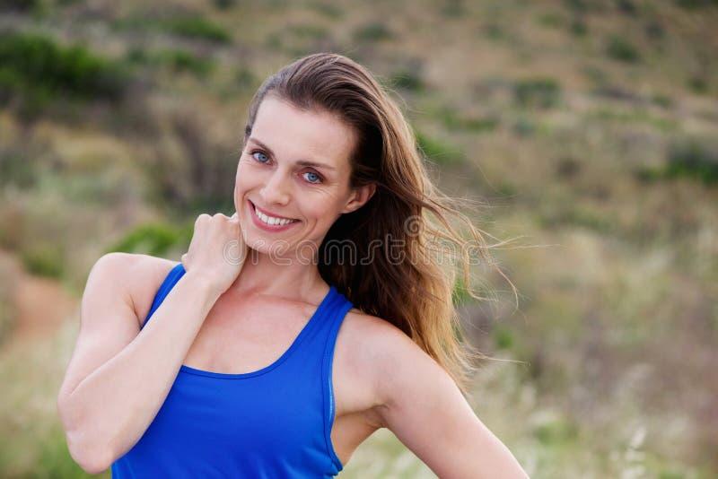 Lächelnde aktive Frau, die draußen steht stockbilder