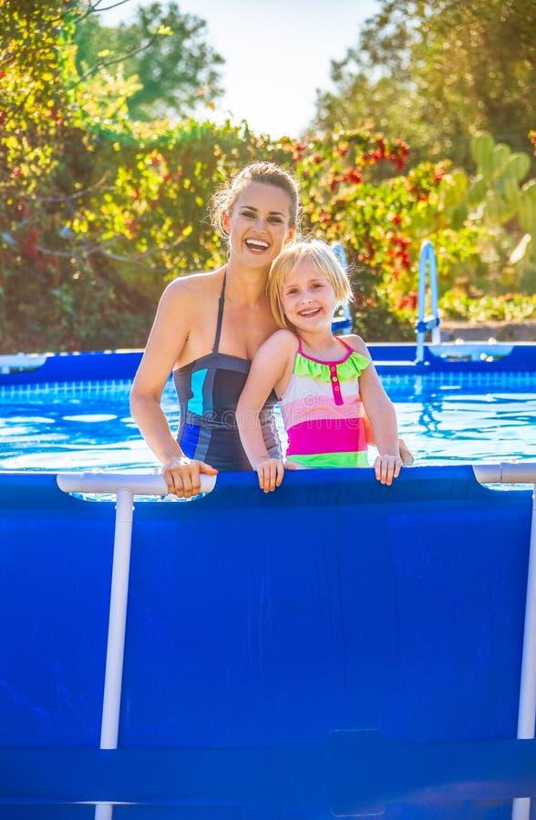 Lächelnde aktive Mutter und Tochter im Swimmingpool stockfotografie
