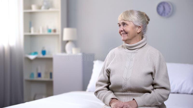 L?chelnde alte Frau, die zu Hause auf Bett, auf Familie Abendessen wartend, Beziehungen sitzt lizenzfreie stockbilder