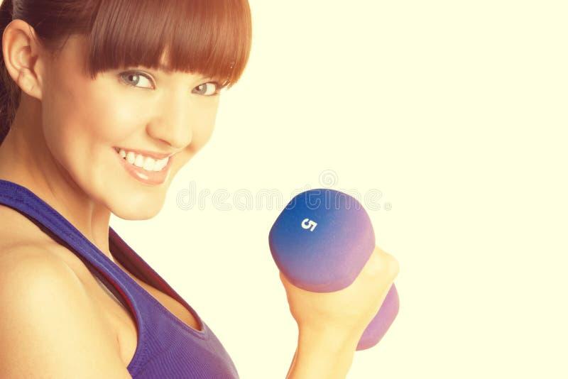 Lächelnde anhebende Gewichte der Frau stockfoto