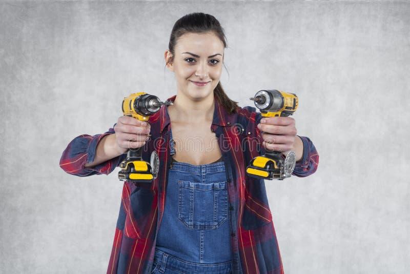 Lächelnde Arbeitnehmerin, die Elektroschrauber hält stockbild