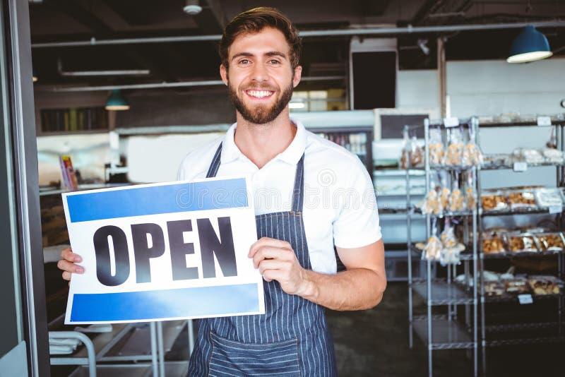 Lächelnde Arbeitskraft, die herauf offenes Zeichen sich setzt lizenzfreie stockbilder