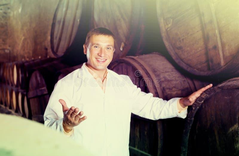 Lächelnde Arbeitskraft, die mit Weinfässern aufwirft stockbild