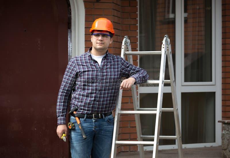Lächelnde Arbeitskraft im Schutzhelm, der an der Metallleiter sich lehnt stockfoto