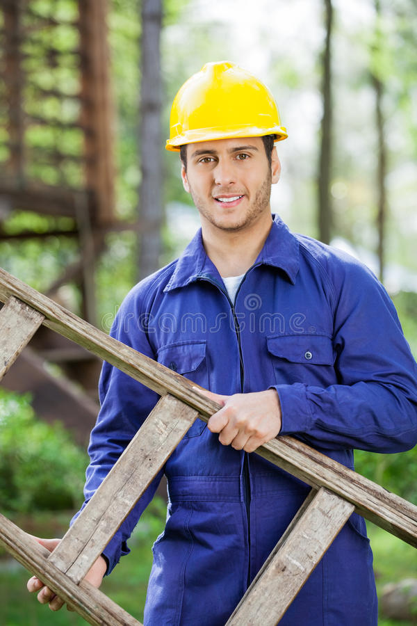 Lächelnde Arbeitskraft-tragende Leiter am Bau stockfotos