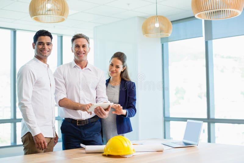 Lächelnde Architekten, die über digitaler Tablette im Konferenzsaal sich besprechen lizenzfreie stockfotografie