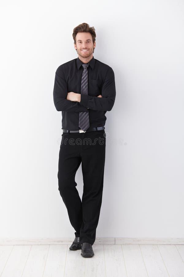 Lächelnde Arme des überzeugten Geschäftsmannes gekreuzt lizenzfreie stockbilder