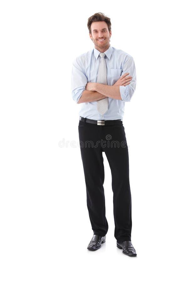 Lächelnde Arme des überzeugten Geschäftsmannes kreuzten stockfoto