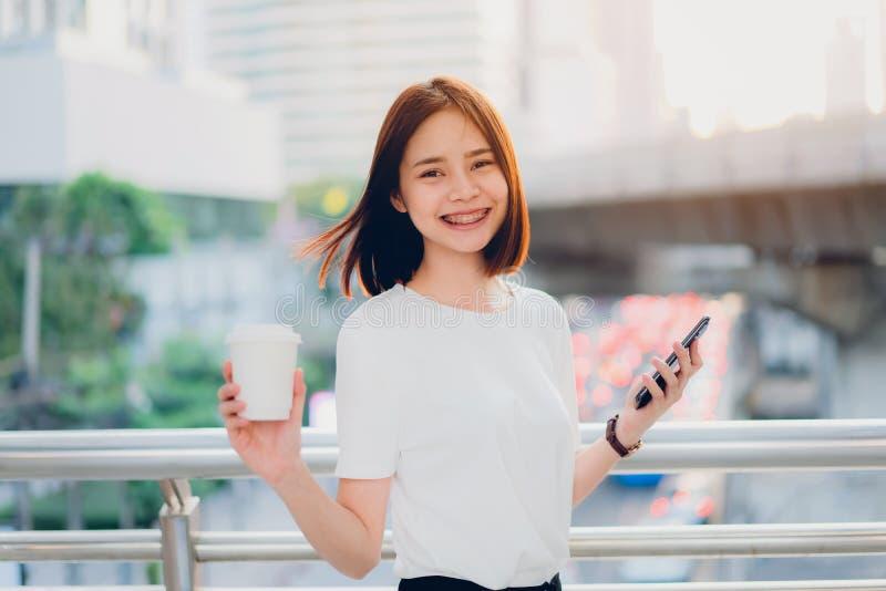 Lächelnde Asiatin, die die Kaffeetasse und Anwendung von Smartphone in bedecktem Gehweg hält Hintergrund ist ein Straße bokeh Ver lizenzfreies stockfoto