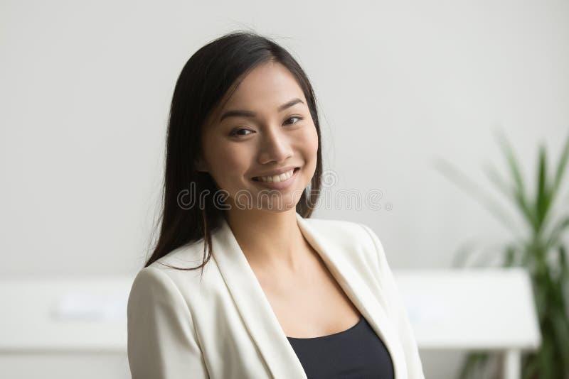 Lächelnde asiatische Arbeitskraft, die zur Kamera aufwirft stockfotos