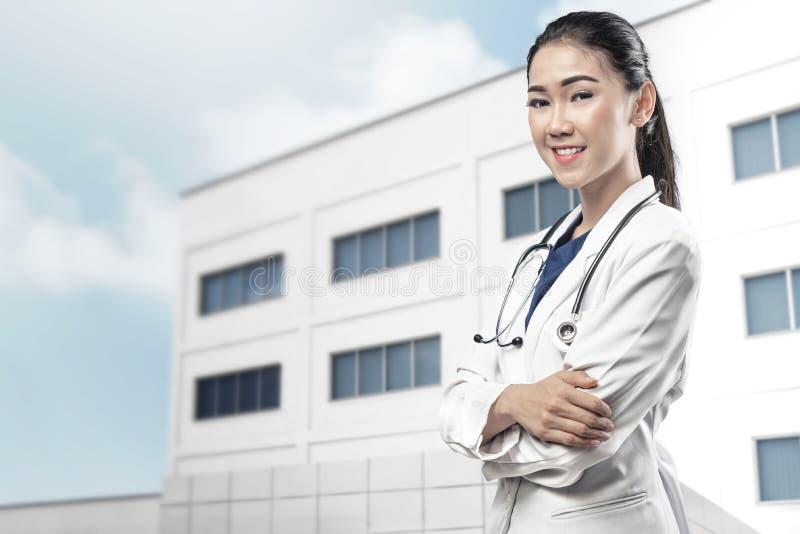 Lächelnde asiatische Doktorfrau im weißen Laborkittel und im Stethoskop lizenzfreies stockfoto