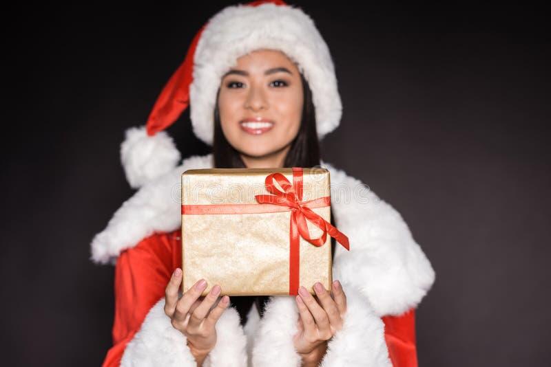 lächelnde asiatische Frau im schwarzen Badeanzug und in Sankt-Kostüm, ein Geschenk und ein Schauen zeigend stockfotografie