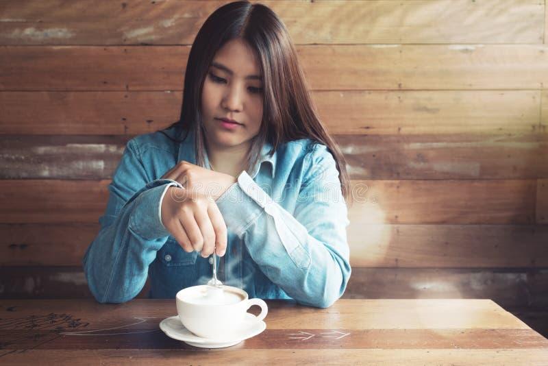 Lächelnde asiatische Frau mit heißer Kaffeetasse an der Kaffeestube lizenzfreies stockfoto