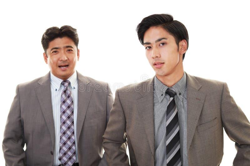 Lächelnde asiatische Geschäftsmänner stockfotos