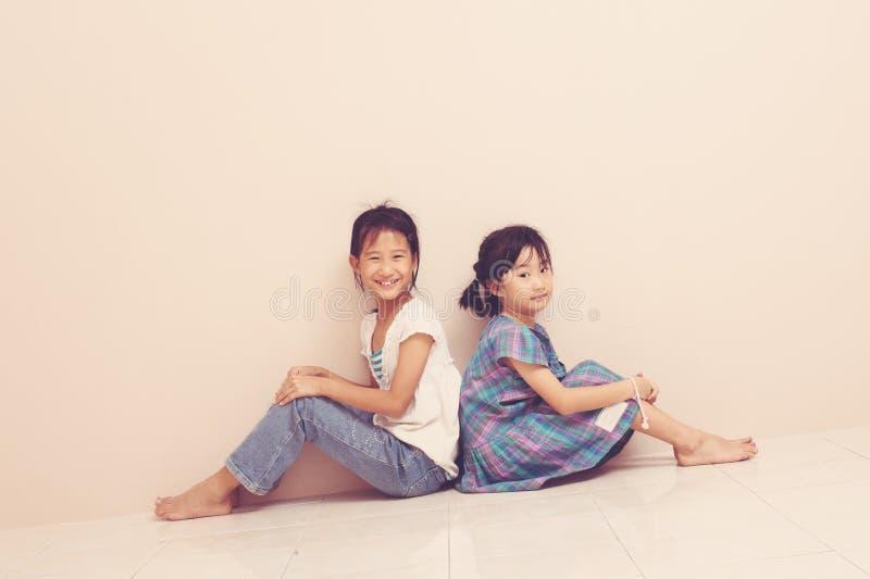 Lächelnde asiatische Geschwister mit ihren Rückseiten sitzen und sich berühren Reizende aufrichtige Gefühle von der Kindheit lizenzfreies stockfoto