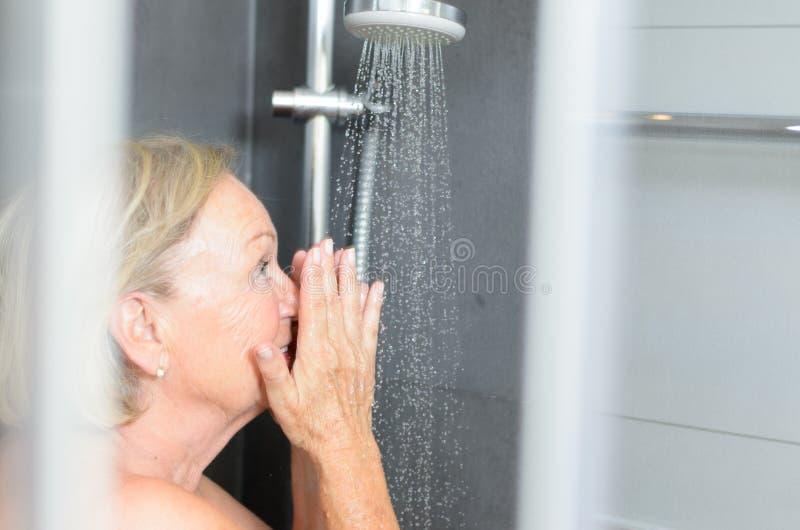 Lächelnde attraktive ältere Frau, die eine Dusche nimmt stockbild