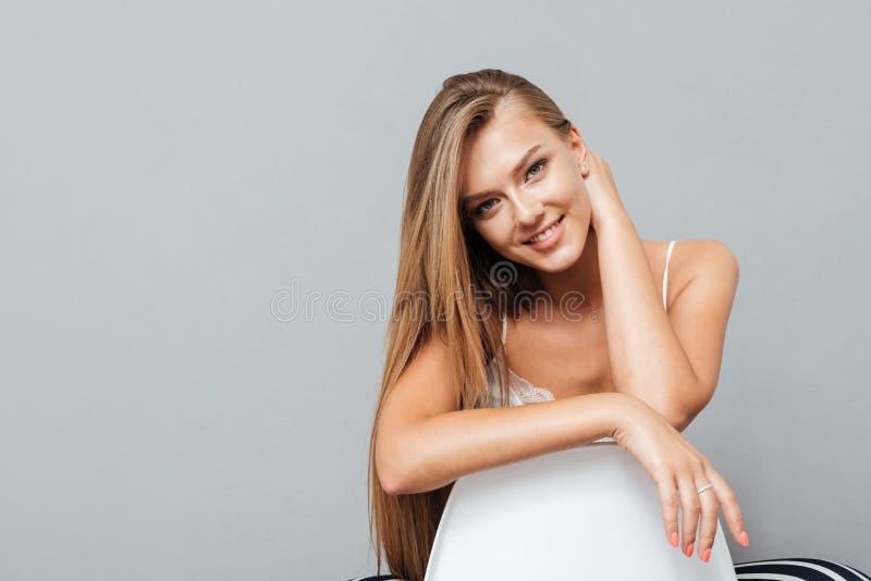 Lächelnde attraktive Frau, die auf dem Stuhl sitzt stockfoto