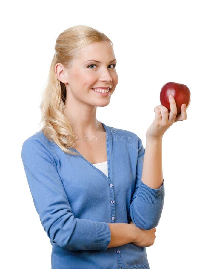 Lächelnde attraktive Frau, die roten Apfel anhält lizenzfreie stockbilder