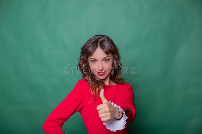 Lächelnde attraktive Frau im roten Kleid wirft mit der Hand auf Hüfte auf und zeigt Daumen oben auf grünem Türkishintergrund stockbild