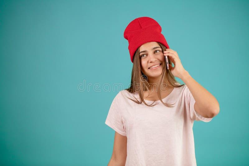 Lächelnde attraktive Frau mit dem langen geraden Haar und roter Kappe spricht am Telefon lizenzfreies stockfoto