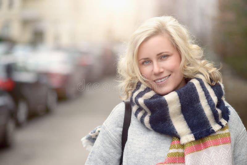 Lächelnde attraktive junge Frau in einem wolligen Schal lizenzfreie stockfotos