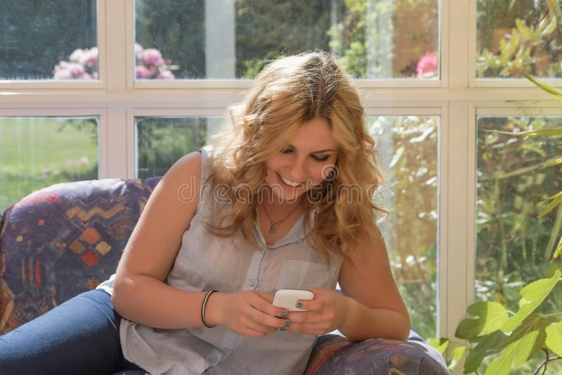 Lächelnde attraktive junge Frau mit intelligentem Telefon lizenzfreie stockfotografie