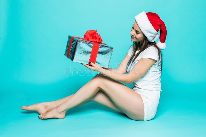 Lächelnde attraktive junge Frau in Weihnachtsmann-Hut, der Präsentkarton lokalisiert auf dem Farbhintergrund sitzt und hält stockfotografie