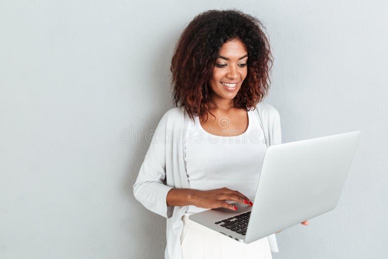 Lächelnde attraktive zufällige afrikanische Frau, die Laptop-Computer verwendet stockbild
