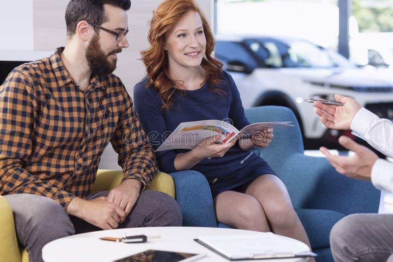 Lächelnde aufpassende Broschüre der Paare im Autosalon bei der Unterhaltung mit Händler lizenzfreies stockbild