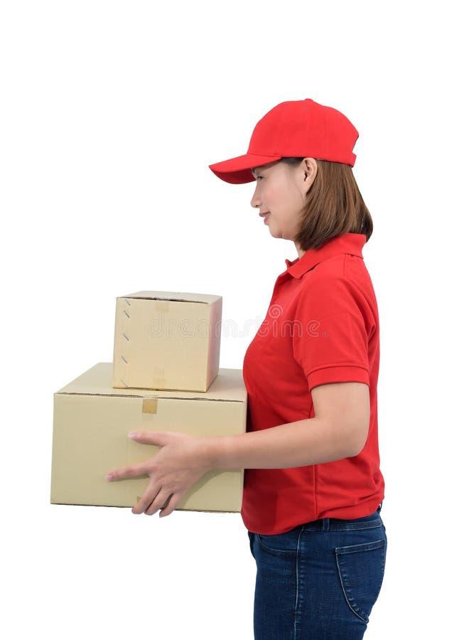 Lächelnde Austrägerin in der roten Uniform, welche die Paketkästen, lokalisiert auf weißem Hintergrund gibt stockbilder