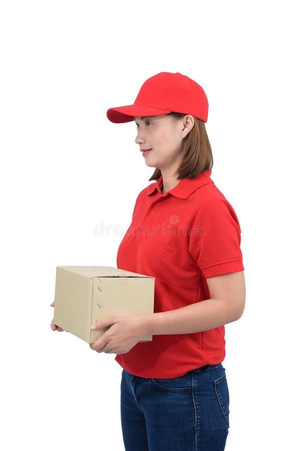 Lächelnde Austrägerin in der roten Uniform, welche die Paketkästen, lokalisiert auf weißem Hintergrund gibt lizenzfreie stockbilder