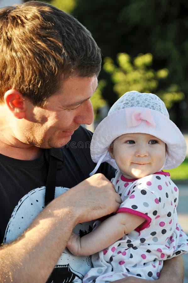 Lächelnde Babytochter in einem Hut mit ihrem Vater stockfoto