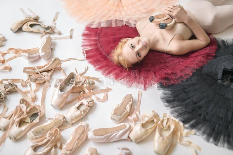 Lächelnde Ballerina liegt auf den bunten Ballettröckchen auf dem weißen Boden lizenzfreie stockfotos